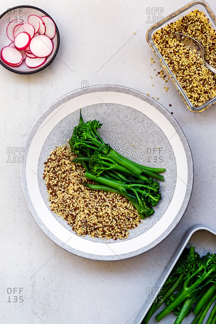 Quinoa, dark green vegetables and radishes as ingredients of Buddha bowl served on plate