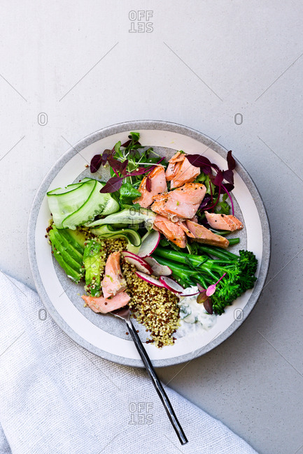 Half eaten Salmon Buddha bowl arranged with linen napkin on tabletop