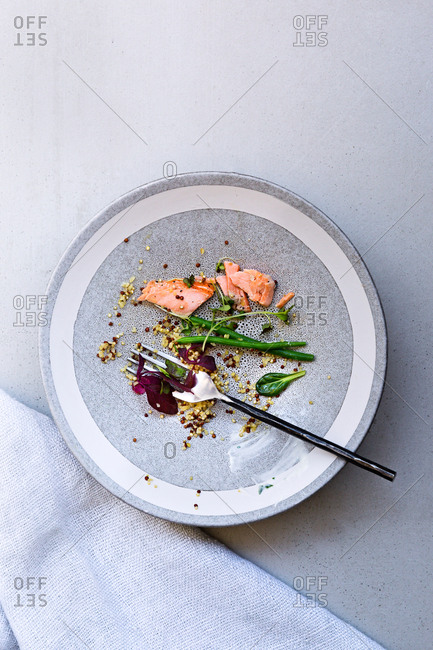 Remains of Salmon Buddha bowl with linen napkin on tabletop