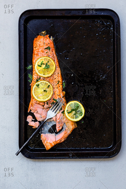Half eaten salmon fillet and lemon slices with fork on roasting tray