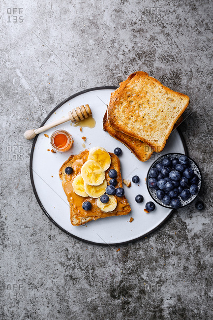 Toast with peanut butter, honey, sliced banana and blueberries