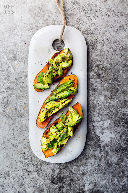 Sliced avocados laid on sweet potato toast