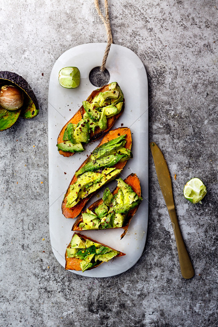Chopped avocados and lime laid on sweet potato toast