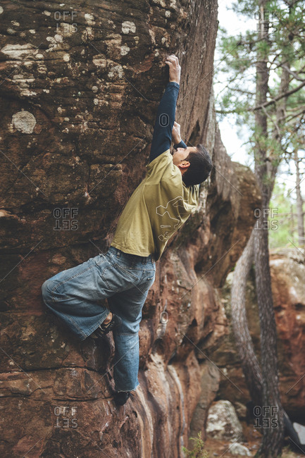 Albarracin, Spain - December 7, 2008: Rock climber climbing on an overhanging boulder