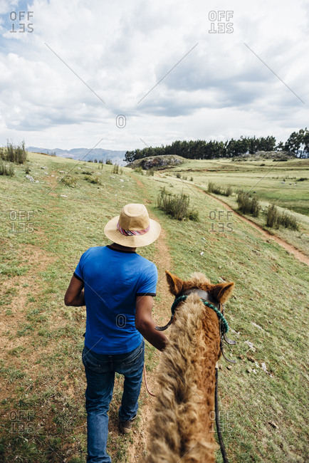 Cuzco, Peru - November 21, 2017: Inca man in hat with horse from behind and above against landscape