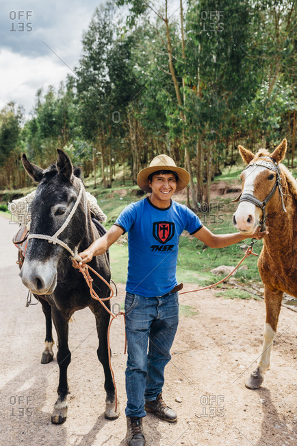 Cuzco, Peru - November 21, 2017: Inca man in hat with two horses
