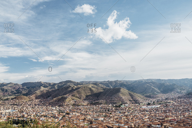 View of Cuzco city and mountains from above with blue sky