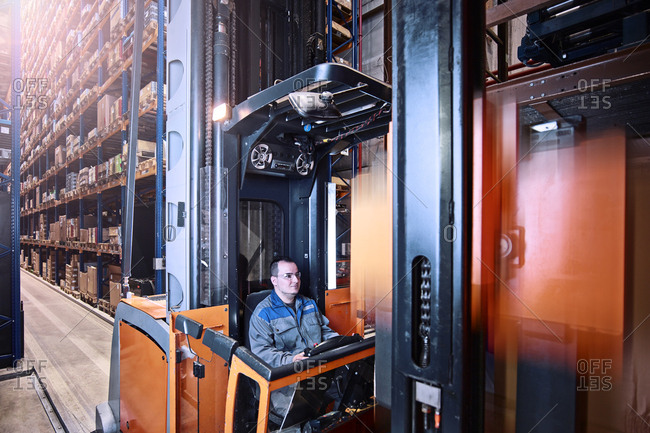 Worker operating high rack in storehouse