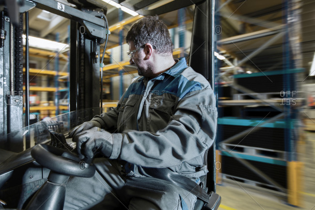 Fork-lift driver in motion in storehouse
