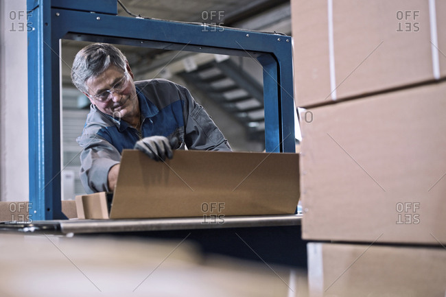 Worker at machine closing packages