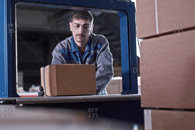 Worker watching machine closing packages