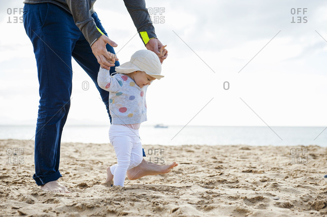 Spain- Lanzarote- baby girl walking on the beach with the help of his father
