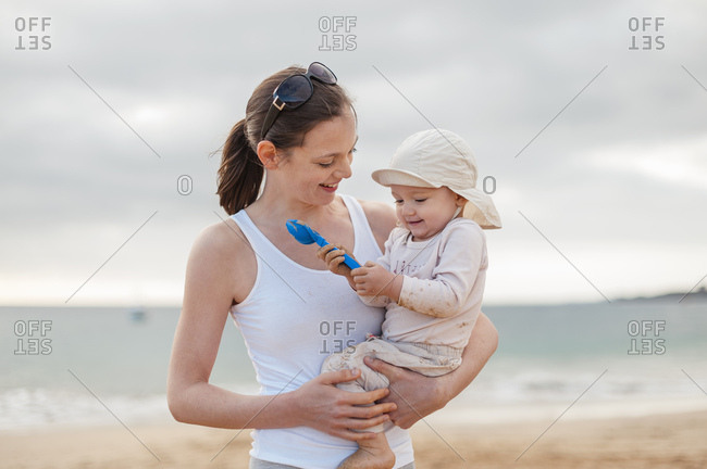 Mother holding little daughter on the beach