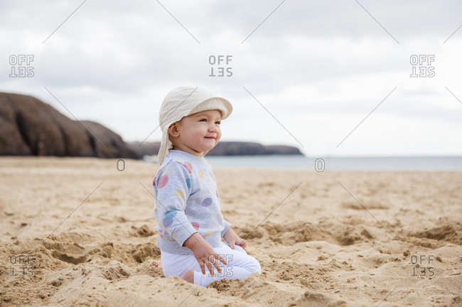 Spain- Lanzarote- content baby girl crouching on the beach