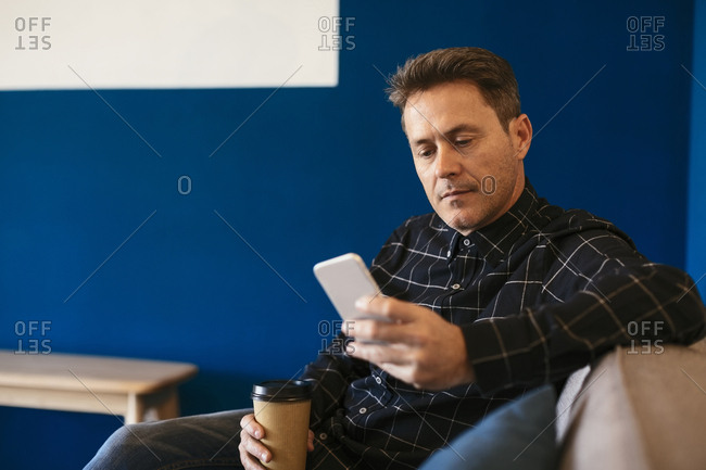 Businessman with takeaway coffee sitting and looking on cell phone
