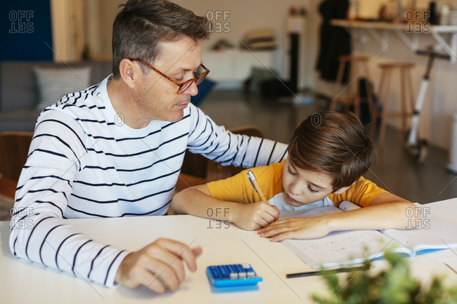 Father watching son doing homework at table