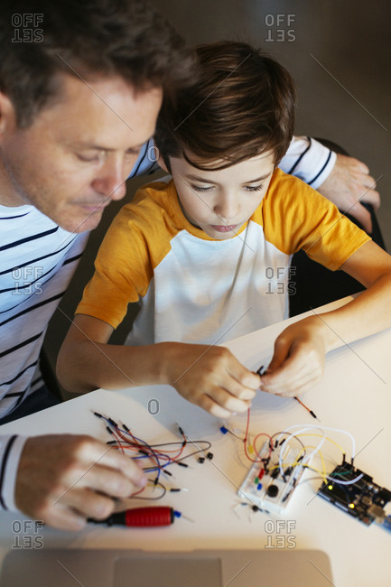 Father and son assembling an electronic construction kit