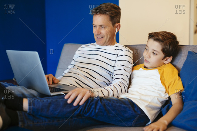Father and son with earbuds and laptop on couch at home