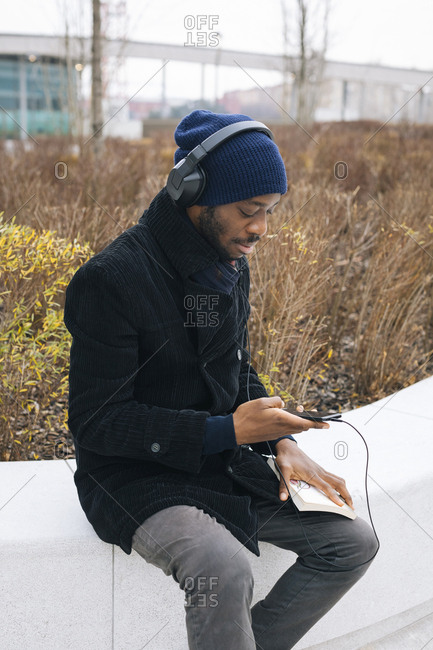 Italy- Milan- African american with smartphone- headphone and book