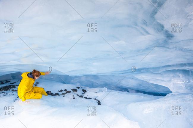 USA- Alaska- Valdez- Valdez Glacier young woman wearing oilskin- exploring ice cave
