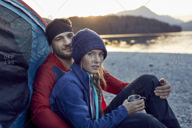 Young couple sitting at tent at lakeshore
