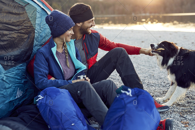 Happy young couple with dog sitting at tent at lakeshore