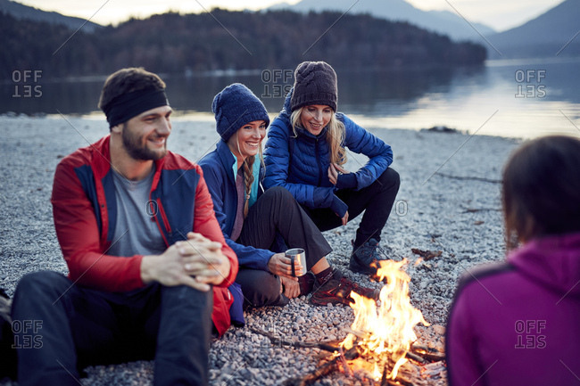 Smiling friends sitting around campfire at lakeshore