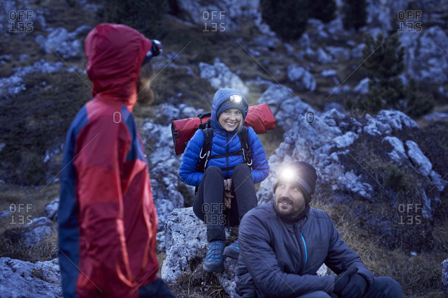 Smiling mountaineers wearing headlamps in the mountains at dusk