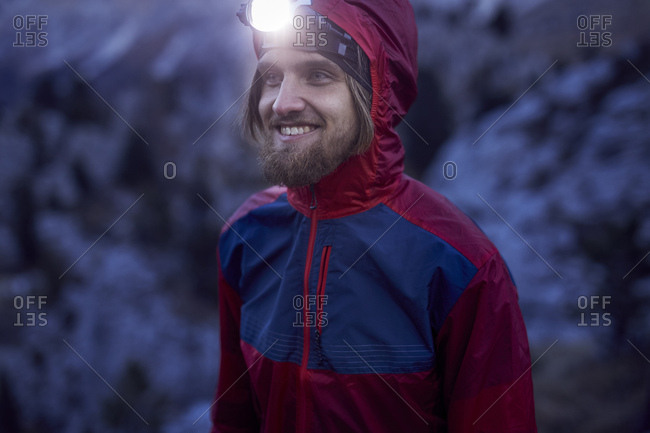 Portrait of smiling man wearing headlamp at dusk in the mountains