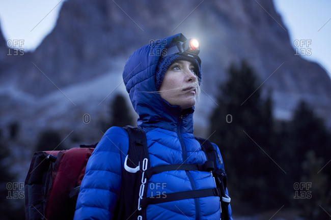 Young woman wearing headlamp at dusk in the mountains