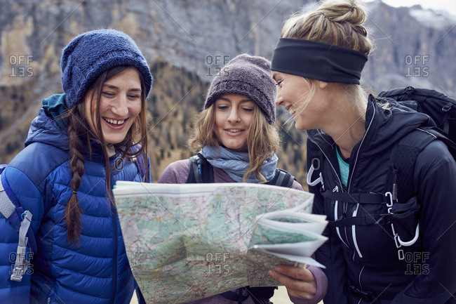 Three happy young women hiking in the mountains looking at map