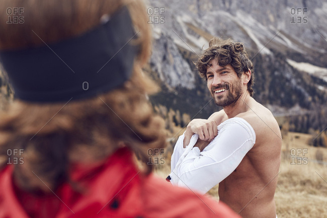 Two trail runners in the mountains changing shirt