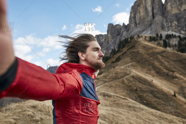 Young man leaning against the wind in the mountains