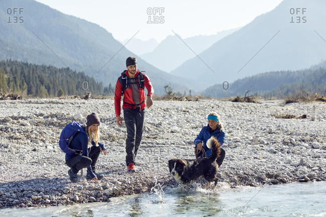 Germany- Bavaria- Karwendel- group of friends hiking with dog at the riverside