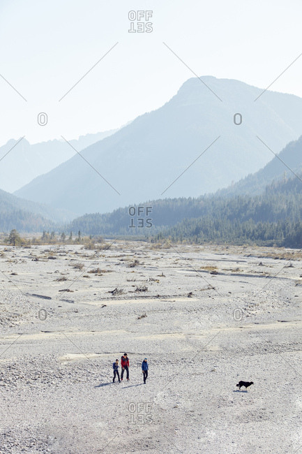 Germany- Bavaria- Karwendel- group of friends hiking with dog in dried riverbed