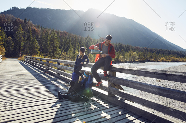 Group of friends with dog hiking resting on a bridge