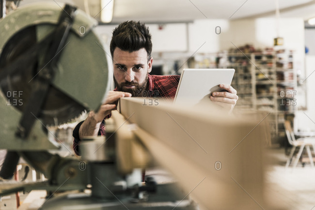 Man in workshop with piece of wood and tablet