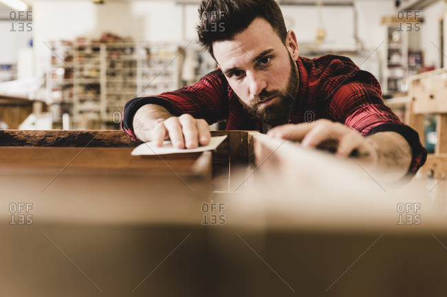 Man treating wood in workshop with sand paper