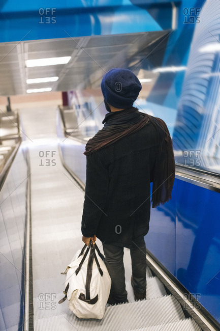 Italy- Milan- African american man with smartphone on escalator