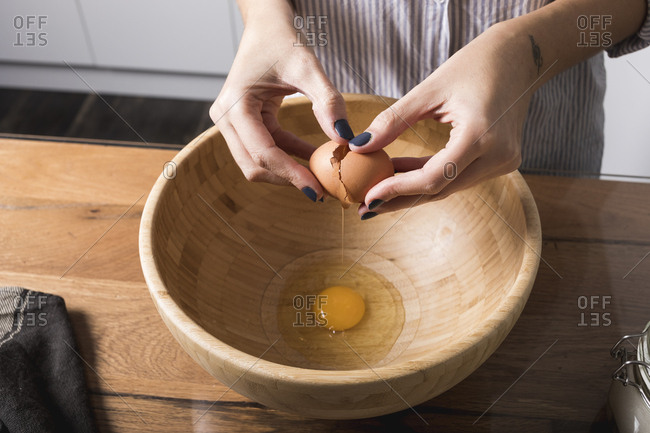 Woman breaking egg- wooden bowl