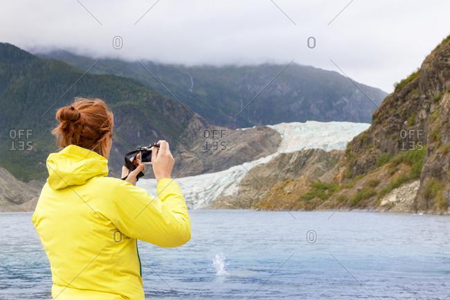 USA- Alaska- Juneau- female tourist photographing Mendenhall Glacier