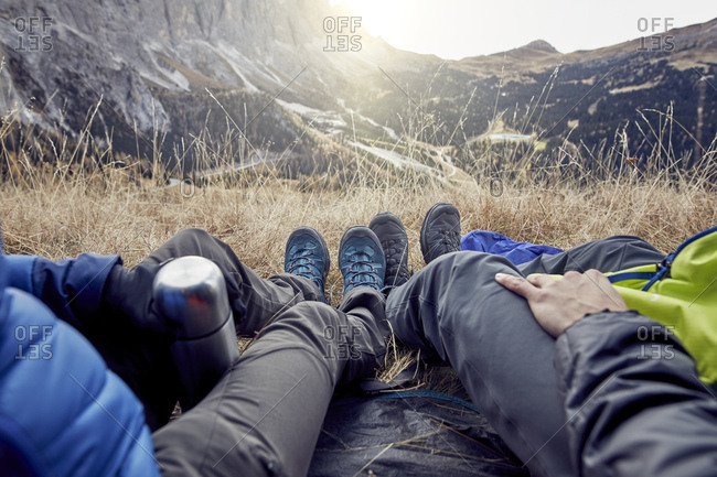 Legs of couple sitting in tent in the mountains