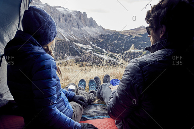 Couple sitting in tent in the mountains looking at view