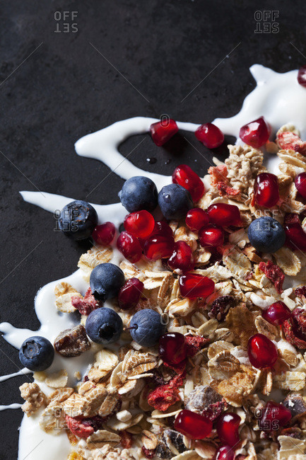 Fruit granola with dried and fresh fruits on yoghurt splash