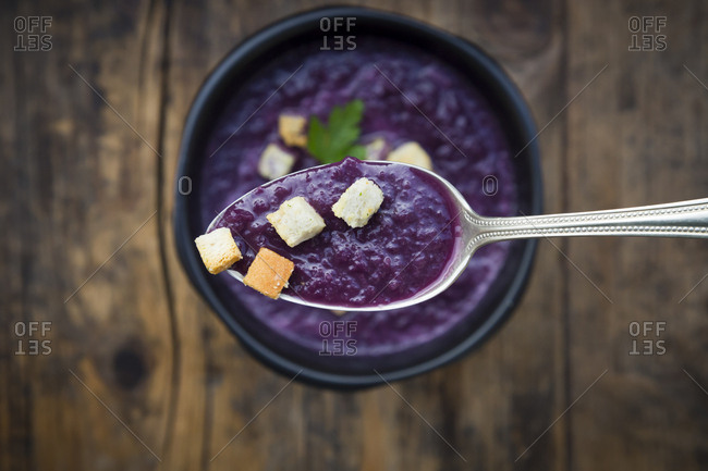 Red cabbage soup and croutons on spoon