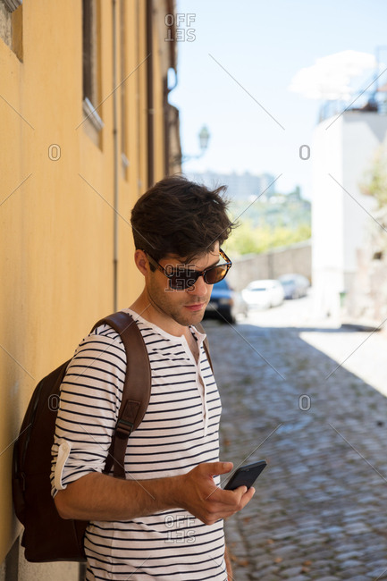 Cute hipster guy looks at phone on a quiet southern European street