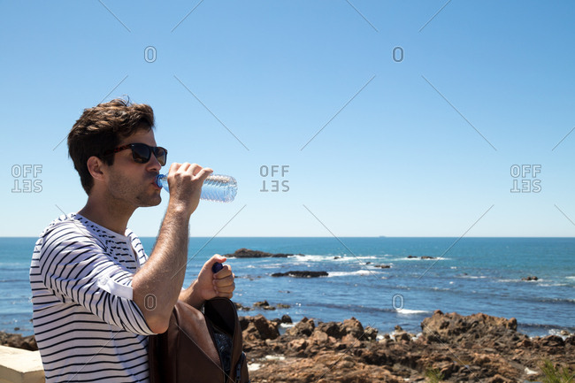 Man drinking water while exploring the oceanside
