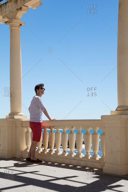 Man gazing at water's edge from a stone promenade