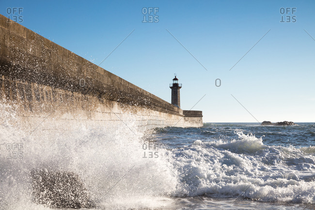Waves crashing on a sea wall and lighthouse in the distance
