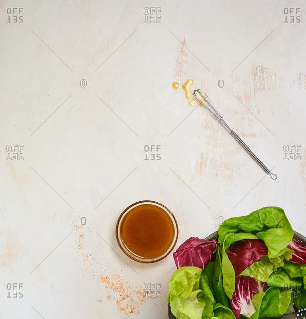 Overhead view of red and green lettuce in a bowl and a side of homemade vinegar dressing